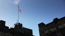 Flag of the United Kingdom blowing in the wind at the top of a castle.