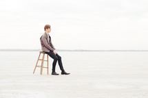 a man sitting on a stool on the great salt plains in Oklahoma