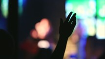 Silhouette of audience with raised hands worshipping at a concert.