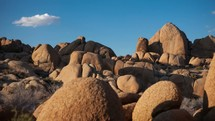 Timelapse of cloud movements and shadows over a rocky desert hillside.