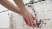 Washing hands with water at a sink faucet.