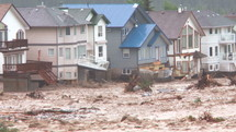 Flood waters rushing through a devastated community.