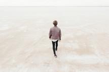 man walking away on sand