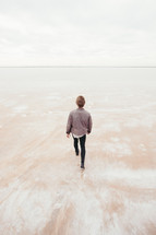 a man walking away over the great salt plains