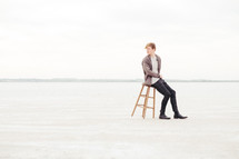 a man sitting on a stool in the great salt plains of Oklahoma