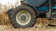tractor driving by crop