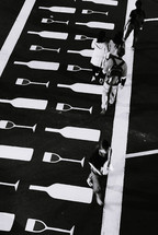 pedestrians on a crosswalk painted with wine bottles