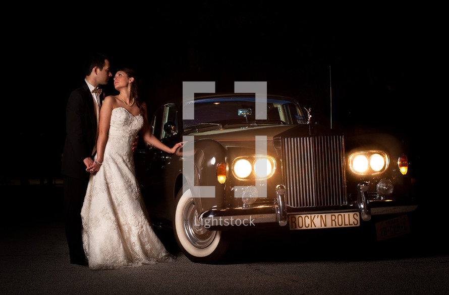 bride and groom standing in front of a vintage rolls royce car