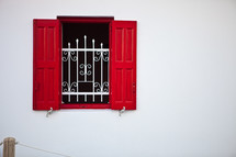 window with wrought iron bars and red shutters