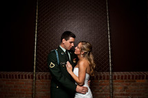 bride and military groom holding each other