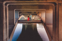 couple holding hands standing under a bridge