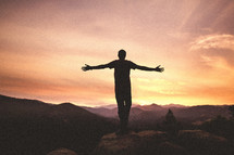 Man's arms raised at the top of mountain at sunset
