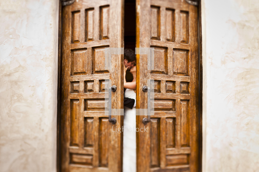 bride and groom kissing behind doors