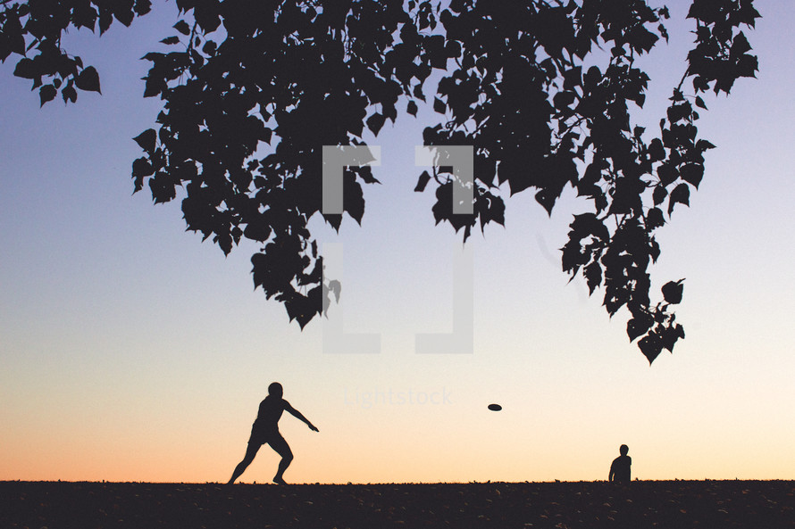 friends playing frisbee in a park