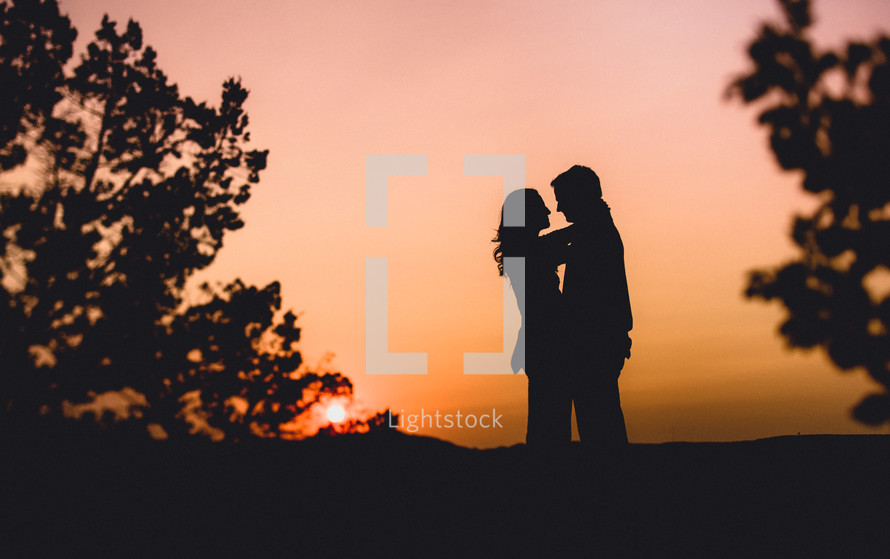 A silhouetted man and woman embracing at dusk.