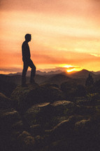 Man standing on rocks at sunset