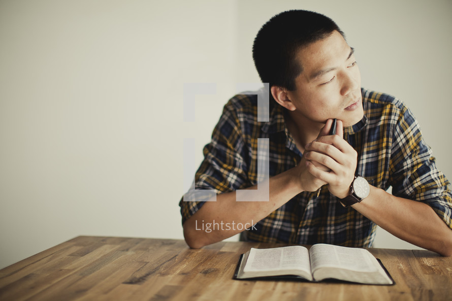 An asian man thinking about scripture
