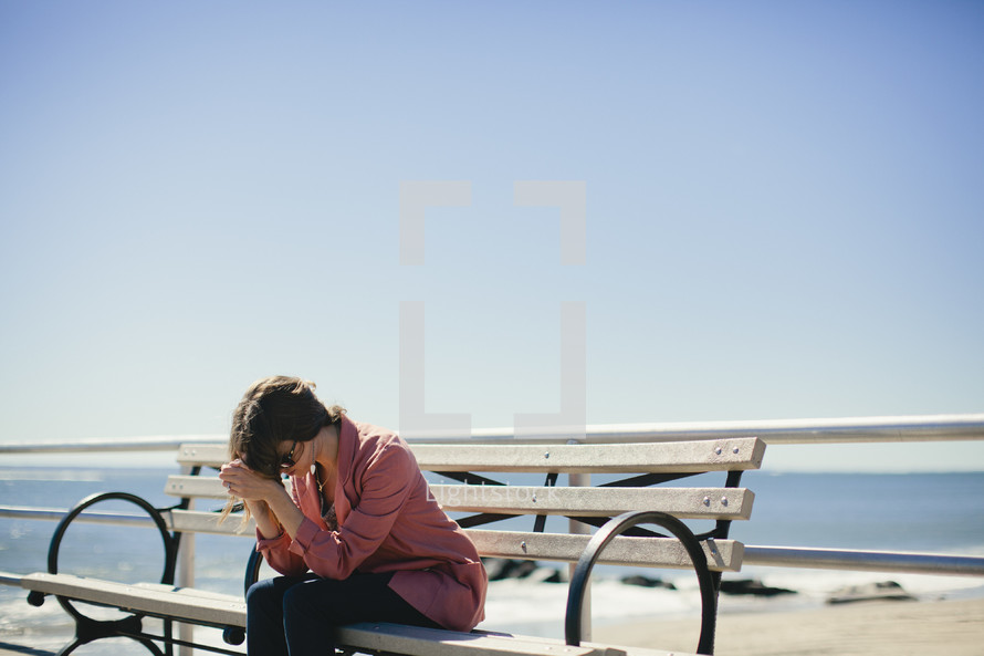 A young woman prays on a park bench