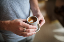 a man holding a coffee with a heart shape