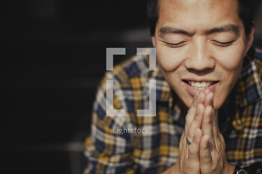 A man with hands touching in prayer