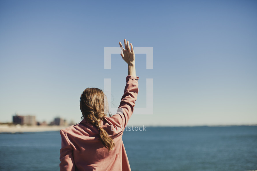 Woman raising arm gazing at ocean