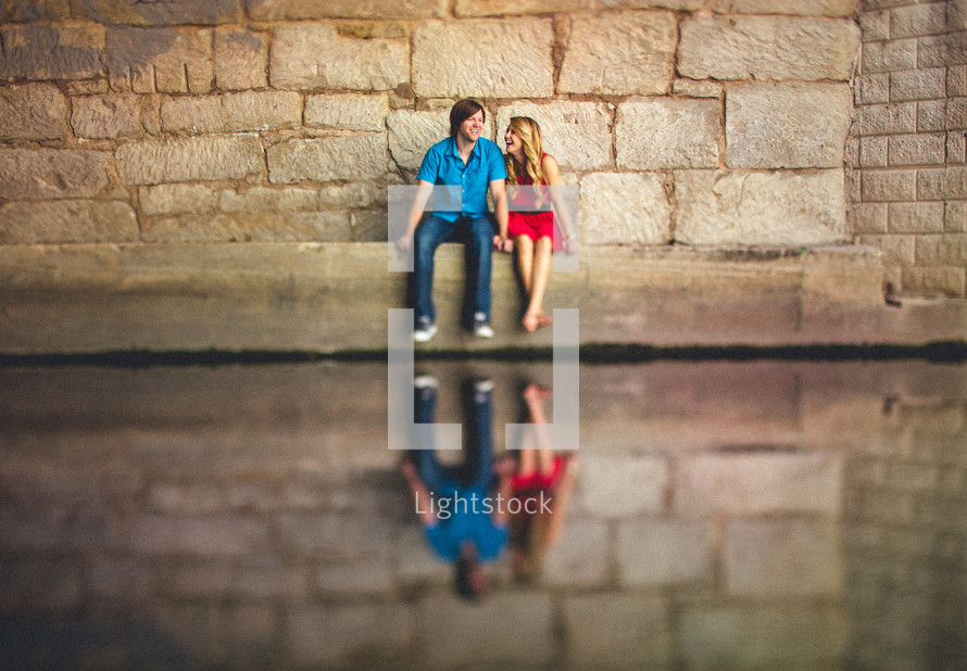 Couple sitting in front of stone wall holding hands