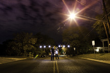 man and woman standing in the middle of a street