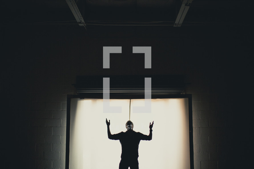 Silhouette of a man with hands raised in worship