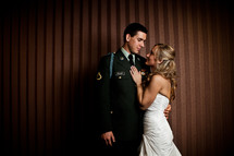bride with her hands on the chest of her military groom