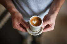 a man holding a coffee with heart shape creamer