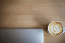 closed laptop and coffee with creamer on a table