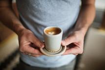 a man holding a coffee with a heart shape creamer shape