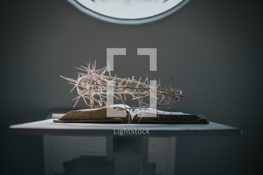 crown of thorns over the pages of a Bible on a stand