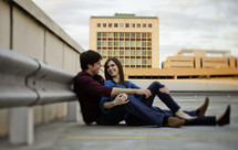 Happy couple sitting in rooftop parking lot
