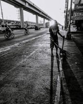 a man sweeping a city sidewalk