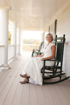 Woman sitting in rocking chair on a porch