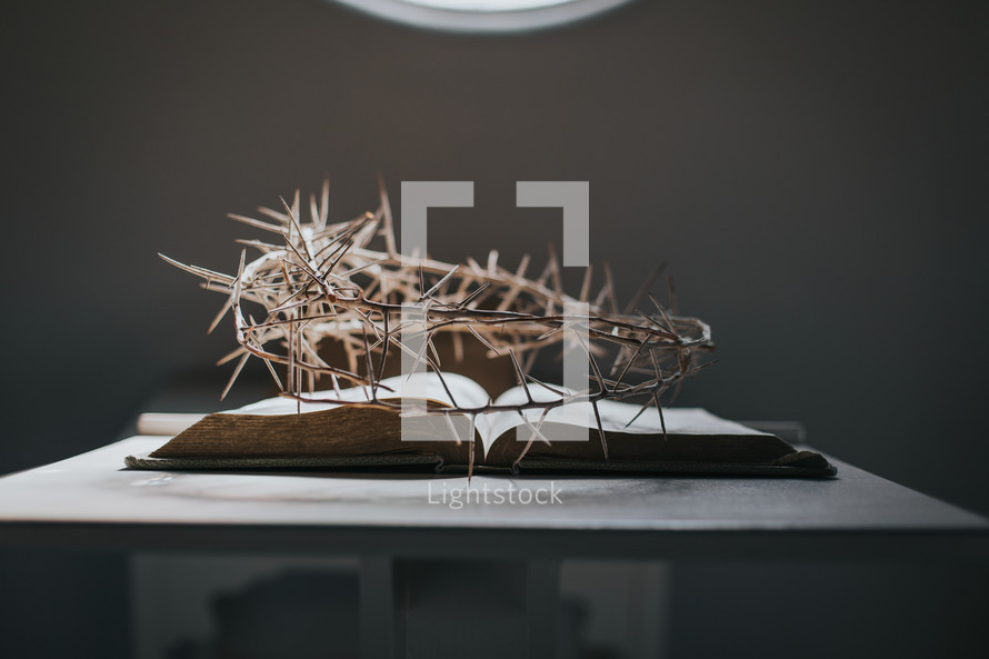 crown of thorns over an open Bible on a stand