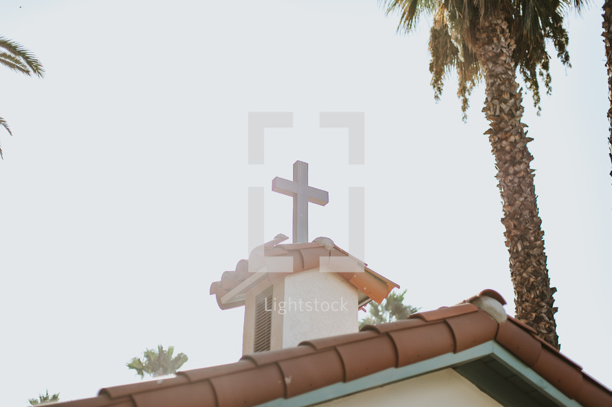 cross topper on the top of a church with a tile roof