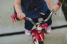 a toddler girl on a red tricycle