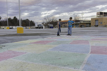 children coloring a parking lot with sidewalk chalk
