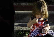 a toddler girl eating jam