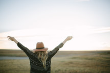 a woman standing outdoors with hands raised in worship
