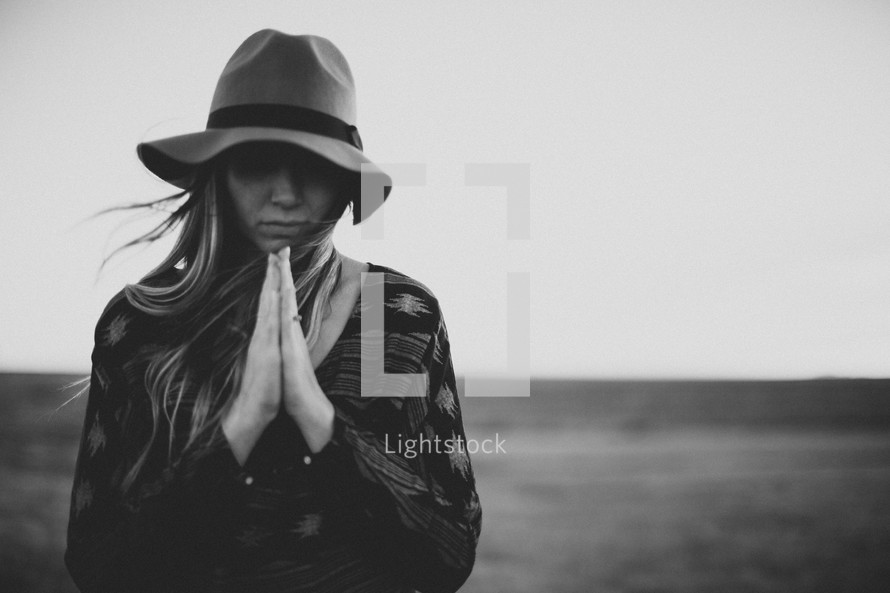 a woman with praying hands and a hat standing outdoors