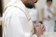 a priest with praying hands