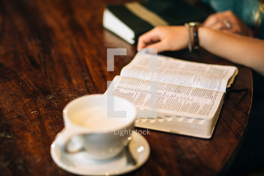 Hands om a wooden table with an open Bible and a cup of coffee.