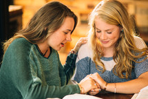 Two women embracing during prayer at a table with Bibles.