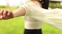 a woman standing with outstretched arms with her shirt blowing in the breeze