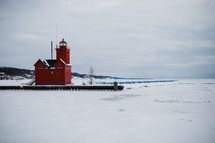 red lighthouse in snow and ice