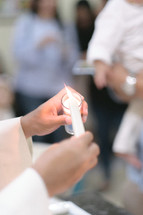 priest lighting a baptismal candle