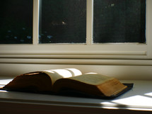 open Bible in a window sill